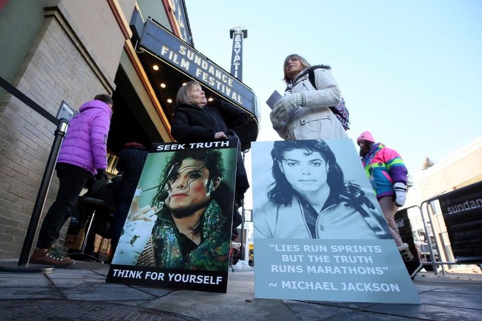 آنچه لازم است درباره مستند جدید مایکل جکسون بدانید ــ در این عکس، که روز 25 ژانویه 2019 گرفته شده است، در سمت چپ برندا جنکینز و کاترین ون تیگم را میبینیم که از شهر کالگری کانادا با ماشینشان راه افتادند و اکنون در ایالت یوتا در پارکسیتی با این تابلوها در خیابان مین، بیرون سالن اجیپشن که فیلم مستند مایکل جکسون با عنوان «ترک نورلند» را در جشنواره فیلم ساندنس 2019 نمایش میدهد ایستادهاند. اعضای خانواده مایکل جکسون روز دوشنبه 28 ژانویه اعلام کردند که «به شدت خشمگین هستند» از اینکه این دو مرد با این مستند جدید درباره خودشان و زدن اتهامات سوءاستفاده جنسی به جکسون توجه دوبارهای به خود جلب کردهاند. خانواده جکسون ضمن انتشار بیانیهای مستند «ترک نورلند» را، که وید رابسون و جیمز سیفچاک دو متهمکننده جکسون در آن بازی کردهاند، محکوم کردند.